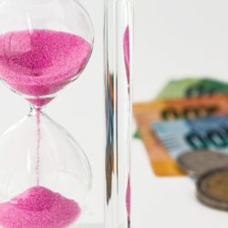 An hourglass next to cash